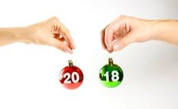 Bij Kerstmisballen die tegen 2018 worden geschreven Handen die Kerstmisbedelaars houden Royalty-vrije Stock Afbeeldingen