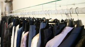 Bij klerenwinkel Rij van mannen en vrouwen kleding jasjes, jeans en overhemden op hangers Inzameling van nieuwe mooi stock videobeelden