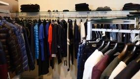 Bij klerenwinkel Rij van mannen en vrouwen kleding jasjes, jeans en overhemden op hangers Inzameling van nieuwe mooi stock video