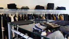 Bij klerenwinkel Rij van mannen en vrouwen kleding jasjes, jeans en overhemden op hangers Inzameling van nieuwe mooi stock footage