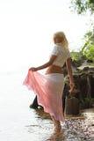 Bij kust loopt en vrouw die achterwaarts kijkt royalty-vrije stock afbeelding