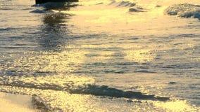 Bij zonsondergang, in de stralen van de zon, de branding golvenbroodje op het zand en uitgespreid over het stock videobeelden