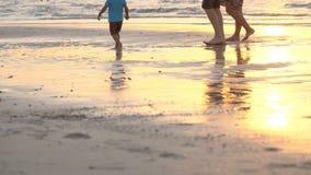 Bij zonsondergang, in de stralen van de zon, wandelt een echtpaar met een klein kind langs het strand, volgens de brandingslijn stock footage