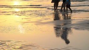 Bij zonsondergang, in de stralen van de zon, wandelt een echtpaar met een klein kind langs het strand, volgens de brandingslijn stock video