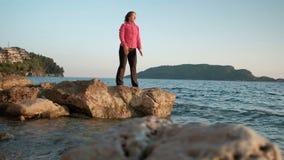 Bij zonsondergang, mediteert een vrouw door het meer die zich op een rots bevinden stock footage