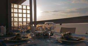 Bij zonsondergang in stad van Perea, Griekenland, diende de dinerlijst met gekookte vissen stock video