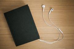 Bijbel aan oortelefoons wordt verbonden die stock foto's