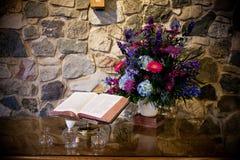 Bijbel en bloemen op lijst Stock Afbeelding
