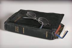 Bijbel en oogglazen stock afbeelding
