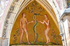 Bijbelscène van Ontstaan met Adam en Eva bij belangrijk ingangsportaal van Heilige Vitus Cathedral in Praag, Tsjechische Republie stock fotografie