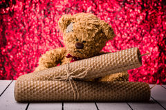 Bijenwaskaarsen en teddybeer op aardige rode achtergrond bukeh Stock Foto