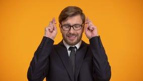 Bijgelovige zakenman die vingers voor goed geluk kruisen, die hopen te winnen, fortuin stock footage