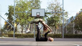 Bijgewoond stelt Van de Appearlings houdende van man en vrouw het praktizeren yoga en stijgende lichaamssterkte stock foto's