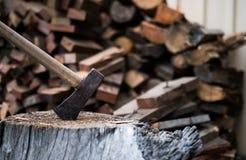 Bijl in houtblok met brandhout Stock Foto's