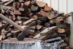 Bijl in houtblok met brandhout Royalty-vrije Stock Afbeeldingen