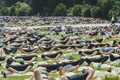 Bijna 2000 mensen nemen een vrije collectieve yogaklasse in een stadspark in Milaan, Italië Stock Afbeeldingen
