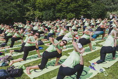 Bijna 2000 mensen nemen een vrije collectieve yogaklasse in een stadspark in Milaan, Italië Stock Afbeelding