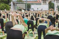 Bijna 2000 mensen nemen een vrije collectieve yogaklasse in een stadspark in Milaan, Italië Stock Fotografie