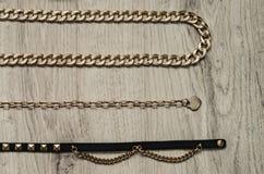 bijouterie的构成,以蛇的形式金链子和与金黄插入物的黑皮带 免版税库存图片