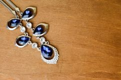 Bijoux argentés femelles avec les gemmes bleues, diamants sur un brun, fond en bois dans le coin gauche supérieur image stock