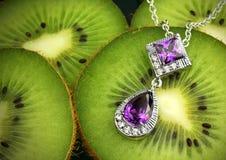 Bijoux colorés avec des gemmes et des diamants sur le backgroun de kiwis Image libre de droits