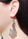 Bijoux de boucles d'oreille avec les cristaux lumineux dans l'oreille Photographie stock libre de droits