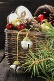 Bijoux de Noël dans un panier sur un fond en bois tonalité Photo stock
