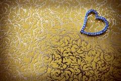 Bijoux en forme de coeur élégants à l'arrière-plan de couleur or. Photographie stock