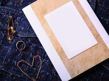 Bijoux et certificat d'or avec l'endroit vide pour la conception sur un fond bleu de denim Photo libre de droits