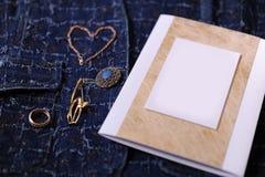 Bijoux et certificat d'or avec l'endroit vide pour la conception sur un fond bleu de denim Photographie stock