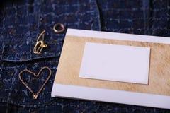 Bijoux et certificat d'or avec l'endroit vide pour la conception sur un fond bleu de denim Photographie stock libre de droits