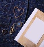 Bijoux et certificat d'or avec l'endroit vide pour la conception sur un fond bleu de denim Photos libres de droits