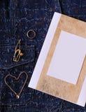 Bijoux et certificat d'or avec l'endroit vide pour la conception sur un fond bleu de denim Photos stock