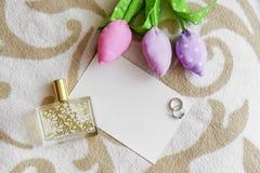 Bijoux et parfum avec la carte et fleurs de femmes sur le sofa Images stock