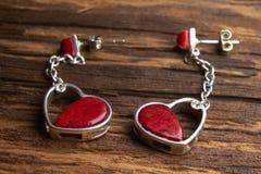 Bijoux féminins - boucles d'oreille argentées sous forme de coeurs avec des pierres de corail rouge photographie stock libre de droits