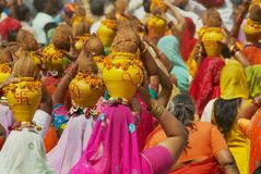 Rajasthani women wearing yellow and red sarees holding coconuts and pots take part in a religious procession in Bikaner, India. Bikaner, India, April 01, 2007 stock photos