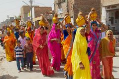 Rajasthani women wearing yellow and red sarees holding coconuts and pots take part in a religious procession in Bikaner, India. Bikaner, India, April 01, 2007 stock photography