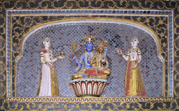 Bikaner palace. Colored statues encrusted with gems of hindu gods and goddesses on blue ceramics background in the Maharajah palace of Bikaner, Rajasthan, India Stock Image