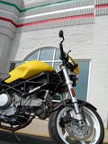 The Bike. Side profile of an Italian motorcyle,  Ducati Monster S2R in front of an Italian themed building Stock Photo