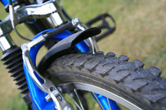 Bike. Close-up of mountain bike wheel on green background Royalty Free Stock Photography