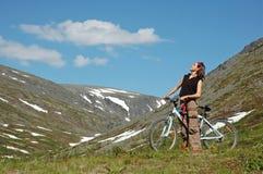 Bike adventure. ! Girl biking in high mountains Royalty Free Stock Photos