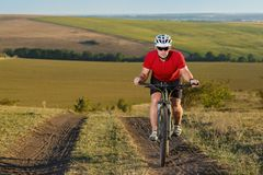 Bike adventure travel photo. Cyclist on the Beautiful Meadow Trail on sunny day. Royalty Free Stock Image