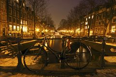 Bike against the bridge in Amsterdam Netherlands. Bike against the bridge in Amsterdam the Netherlands by night Stock Photo