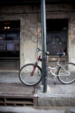 Bike against lamp post in city stock photography