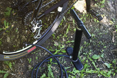Bike and air pump in forest. Repair wheel of bike. Inflation wheels with a pump with a pressure gauge. Stock Photo