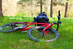 Bike and Backpack Lying on Green Grass Stock Photo
