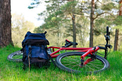 Bike and Backpack Lying on Green Grass Stock Photos