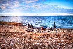 Bike and backpack lying on the wild sea shore. Sunset Stock Photos