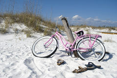 Bike on the Beach. Colorful pink bicycle rests against a tilted post on a gorgeous white sand beach. Image evokes calm, relaxation, and vacation getaway Royalty Free Stock Photo