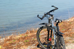 Bike  on the beach. With blue water background Royalty Free Stock Photo